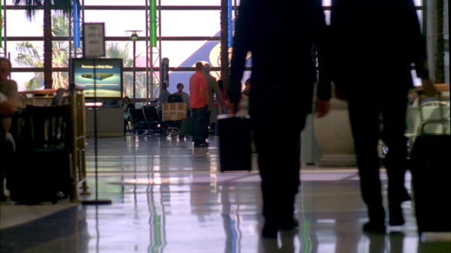 ws airline pilots and passengers walking through airport concourse / los angeles, california, usa - 飛行士点の映像素材/bロール