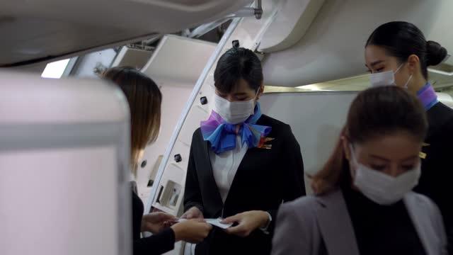 airline stewardess führt sitzplätze für passagiere ein. - passagierflugzeug stock-videos und b-roll-filmmaterial