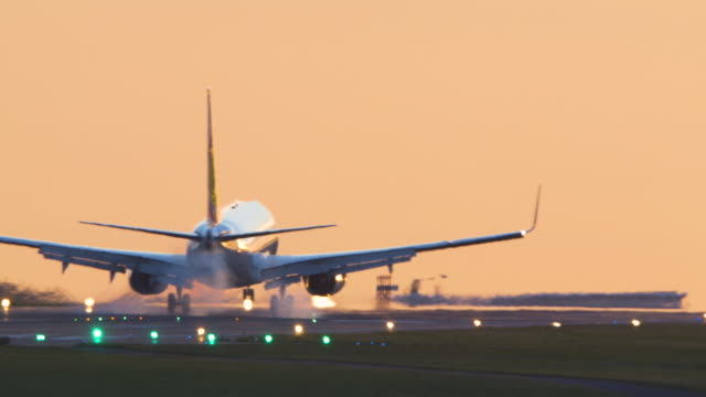 airliner coming in to land with landing lights at sunset. - landing touching down stock videos & royalty-free footage