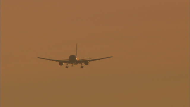 ws pov airliner flying against orange sky  / heathrow airport, london, england - heathrow airport stock videos and b-roll footage
