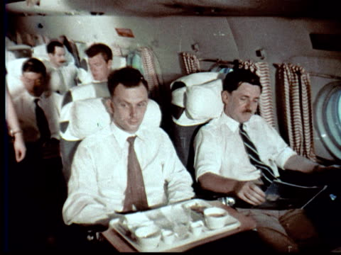 1957 montage airliner flying. interior, flight attendant takes empty dinner tray from man. couple holding hands woman + man look out window / singapore / audio - 1957 stock videos & royalty-free footage