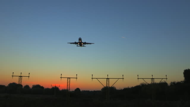 vídeos de stock e filmes b-roll de airliner on approach to runway - anoitecer