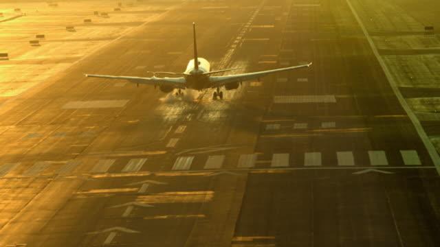 airliner passenger jet landing on airport runway at dusk creating a wavy pattern of air turbulence around aircraft