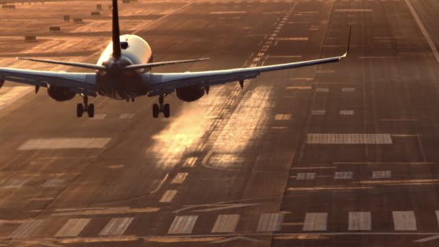 vídeos de stock, filmes e b-roll de ha ws airliner passenger jet landing on airport runway in late afternoon sunlight casting shadow of plane onto runway / san diego, california, usa  - aterrissando