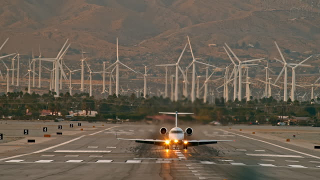 ls airliner passenger jet plane landing on airport runway against background of renewable energy wind farm and automobiles on highway - palm springs california stock videos & royalty-free footage