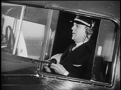 vidéos et rushes de b/w 1933 airliner pilot in headphones + uniform flipping switches + talking into radio (thru window) - avion de tourisme