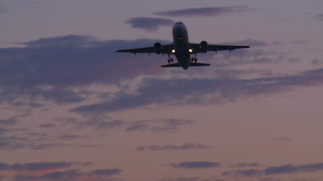 airliner taking-off at sunset. - crew stock videos & royalty-free footage
