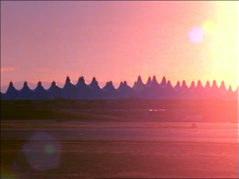 stockvideo's en b-roll-footage met airliner taxiing past camera on runway at sunset / airport buildings in background / denver, colorado - dia