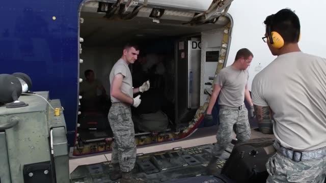 vidéos et rushes de airmen at dyess load onto commercial plane, land at raf fairford and unload cargo. - décharger