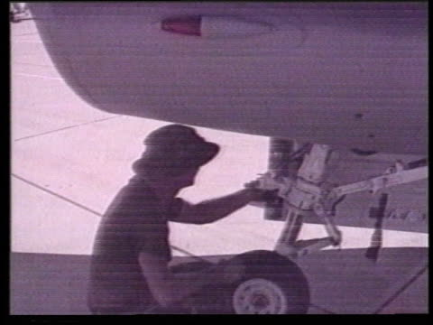 airmen inspect an f-16 as it's refueled on a tarmac. - 給油点の映像素材/bロール