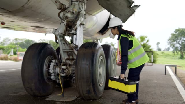 airplane asian engineer maintenance repairs,inspect and work on airplane jet engine in hangar. - airplane hangar stock videos & royalty-free footage