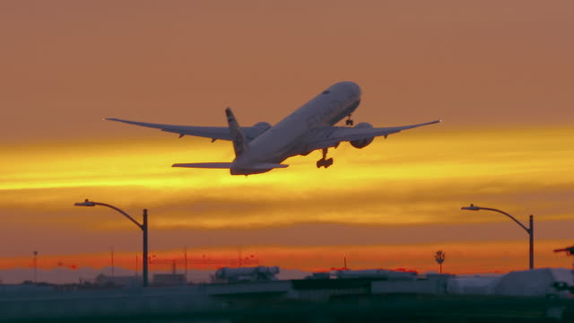 airplane at sunset - taking off stock videos & royalty-free footage