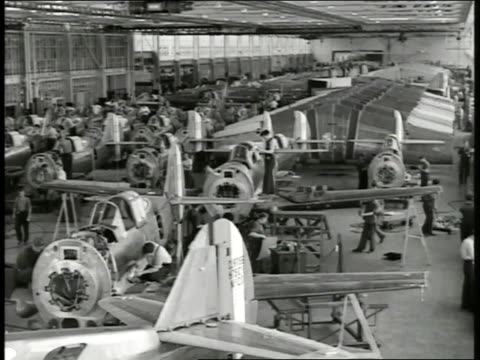 Airplane bodies on warehouse floor men working on airplanes wings lined up BG Mechanic working on wing interior w/ tool Engineers working on paper...