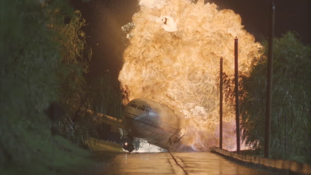 ms, cu, airplane crashing on highway, hitting electricity pole and exploding at night  - rutschen stock-videos und b-roll-filmmaterial