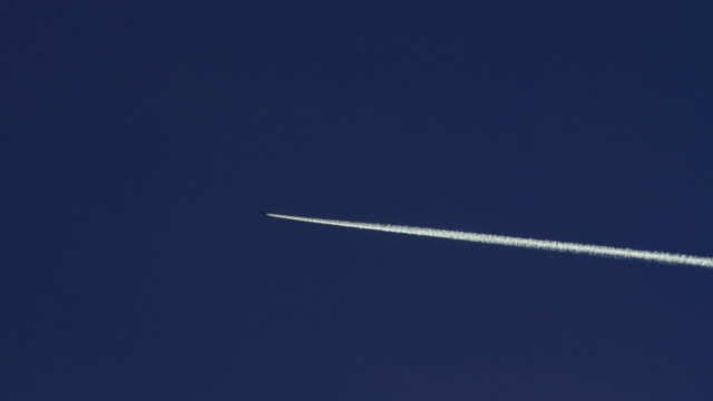 airplane crosses blue sky leaving thick white contrail - hoch position stock-videos und b-roll-filmmaterial