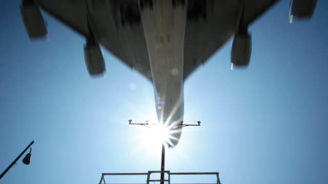 stockvideo's en b-roll-footage met airplane crossing sun - dichterbij komen