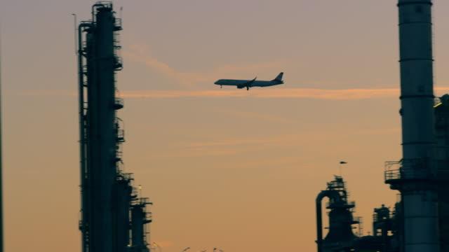 vidéos et rushes de avion de ms descendant dans le ciel de coucher du soleil derrière la raffinerie de pétrole - pétrole