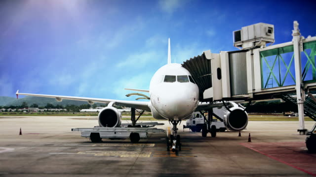 airplane docks at the airport terminal boarding gate with against blue sky. - campo d'aviazione video stock e b–roll