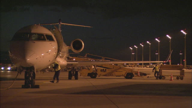 WS ZI Airplane door and steps opening while ground crew work nearby on airport runway at night / Munich, Germany