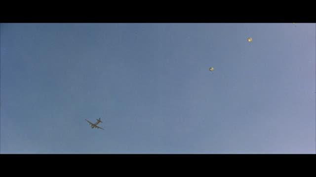 stockvideo's en b-roll-footage met ws airplane drops parachute supplies - breedbeeldformaat