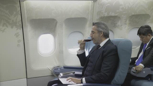 vídeos de stock, filmes e b-roll de cabine de classe econômica de avião com passageiros nos assentos. comissárias de bordo servem comida e bebidas aos passageiros. - vestuário de trabalho formal