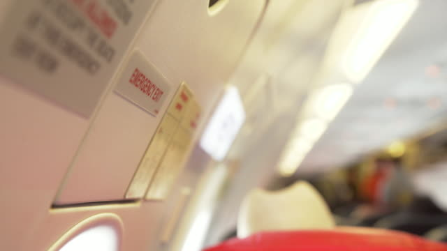 stockvideo's en b-roll-footage met airplane emergency exit red sign - informatiebord