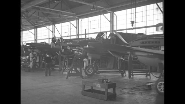 Airplane factory section fuselages and workers on floor can see plane at open door on end / US Army plane taxiing factory building in bg / planes in...