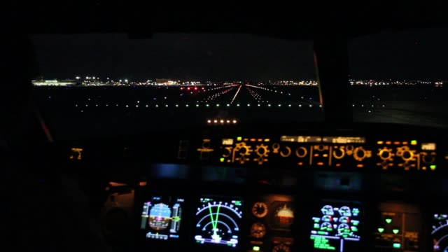 Airplane flight deck lining up with runway at night