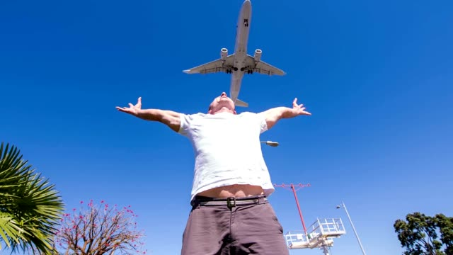 slo mo airplane flying above one mid-adult man - arms outstretched stock videos and b-roll footage