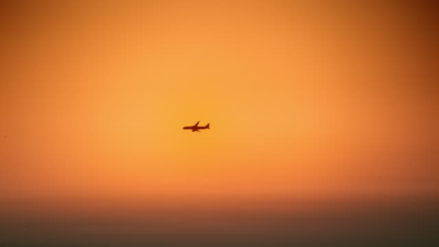 aerial airplane flying across in the orange sky at dusk - distant stock videos & royalty-free footage
