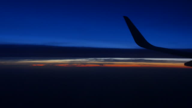 Airplane flying below clouds at pink sunrise