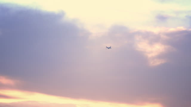 airplane flying on a sunset sky - distant stock videos & royalty-free footage