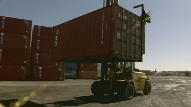 ws airplane flying over yard as container handler lowers cargo container/ sydney, australia - solo un uomo di età media video stock e b–roll