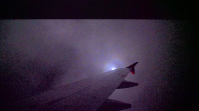 airplane flying through thunder storm cloud at night - aircraft wing stock videos & royalty-free footage