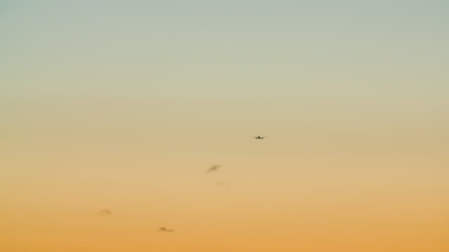 airplane in clear sky at sunset - wide shot stock videos & royalty-free footage