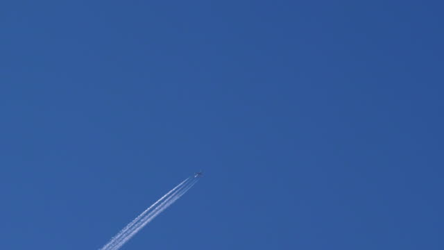 airplane in diagonal flight with four contrails against pale blue sky - vapour trail stock videos & royalty-free footage