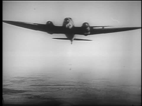 stockvideo's en b-roll-footage met airplane in flight dropping bombs / he 111 / educational - bom