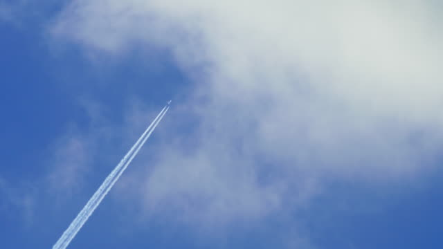 vidéos et rushes de airplane in the sky disappears behind white clouds leaving contrail - avion