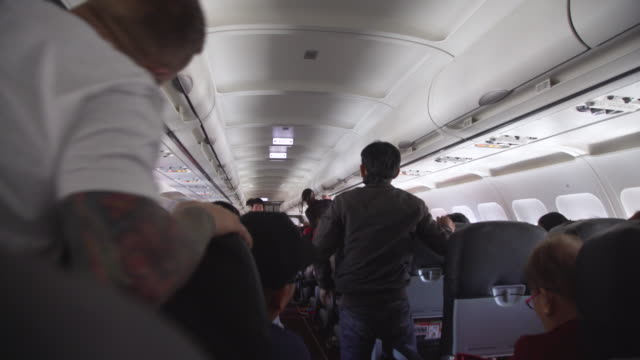airplane indoors. people stand up after landing - exit sign stock videos & royalty-free footage