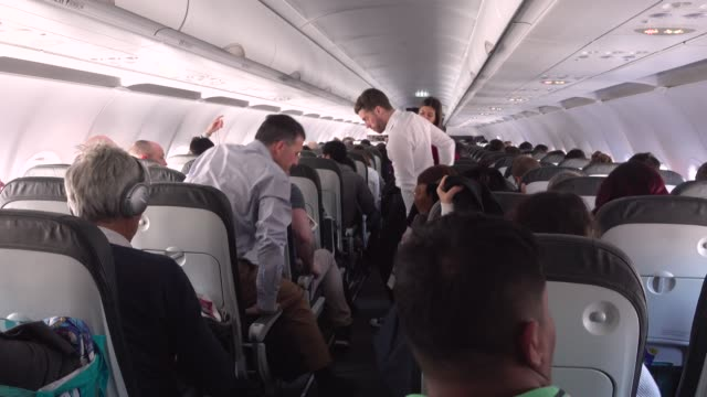 airplane indoors. people standing up after landing - abitacolo video stock e b–roll