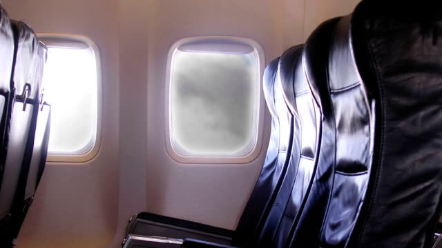 Airplane interior and window with clouds