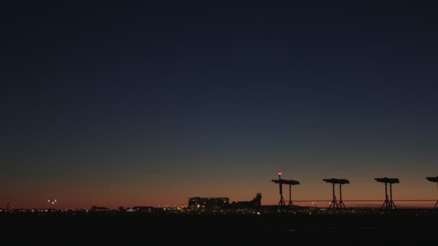 vidéos et rushes de airplane landing at airport at sunset 4k - tour de contrôle