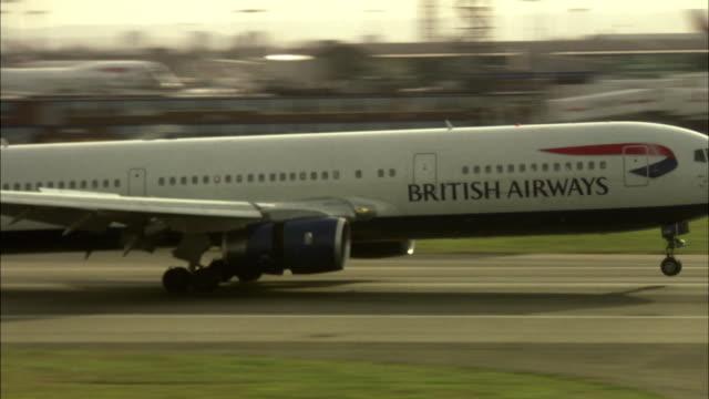 ws pan airplane landing at heathrow airport / london, uk - landing touching down stock videos & royalty-free footage