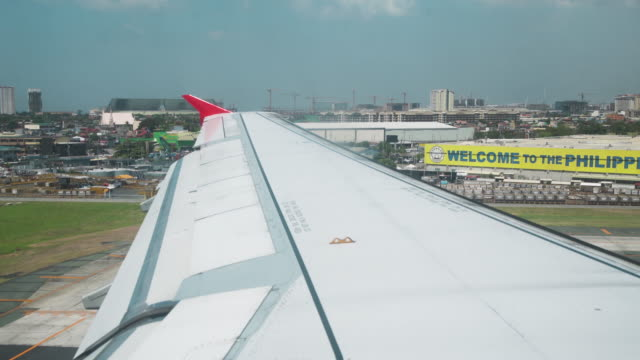 airplane landing at manila airport, philippines - aircraft wing stock videos & royalty-free footage