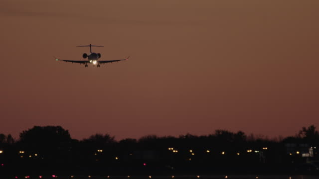 airplane landing at sunset at airport 4k - montreal stock videos and b-roll footage