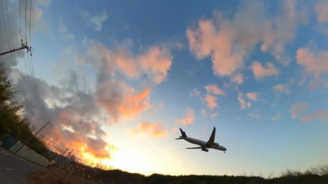 airplane landing at sunset - landing touching down stock videos & royalty-free footage
