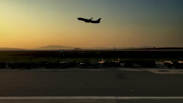 Avião a pousar ao pôr do sol