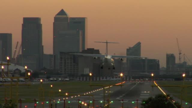 vidéos et rushes de ws, airplane landing on city airport at sunset, london, england - piste d'envol