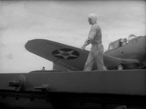 airplane landing on flight deck men rushing to unhook cable la airplane taxiing xws three us battleship on ocean airplane catapulting off cruiser... - anno 1941 video stock e b–roll