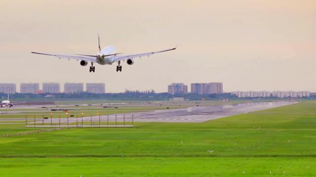 vidéos et rushes de avion atterrissant sur la piste au coucher du soleil - ouest